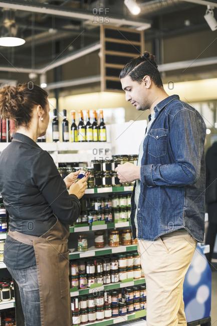 Man buying organic food from saleswoman in supermarket