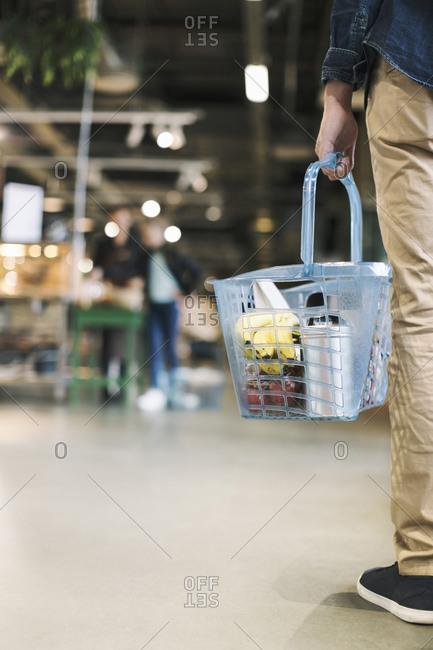 Low section of man carrying grocery basket in supermarket