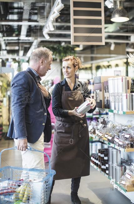 Saleswoman explaining product to mature man in organic supermarket