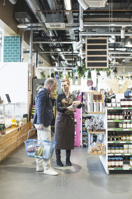 Female owner explaining product to mature man in organic supermarket