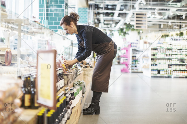 Full length side view of female owner working in supermarket