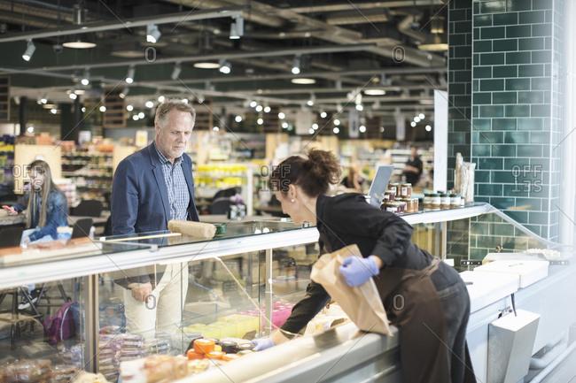 Saleswoman selling food to mature man in organic supermarket