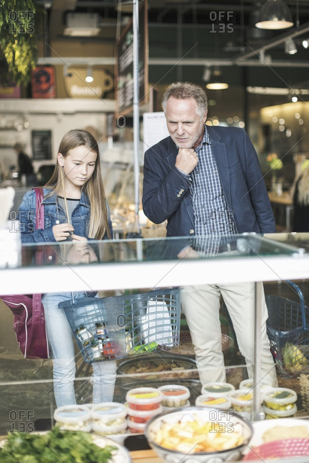 Father and daughter looking in display cabinet while shopping at supermarket