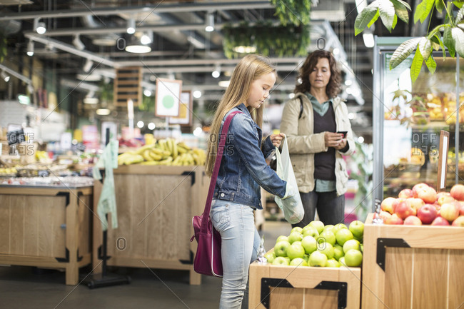 Mother and daughter buying apples in supermarket
