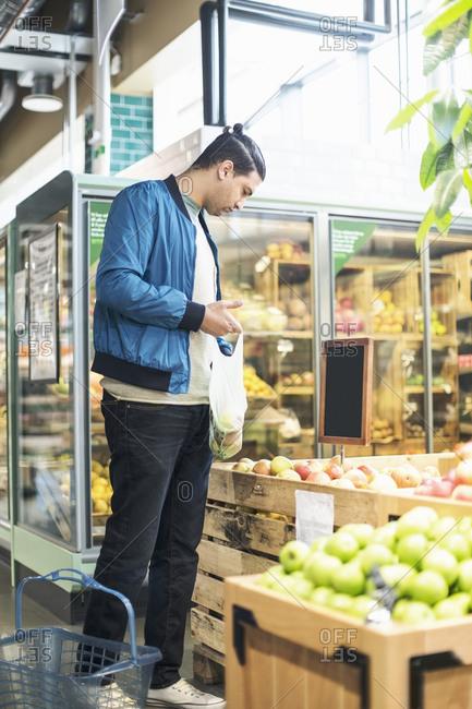 Man buying fruits in organic supermarket