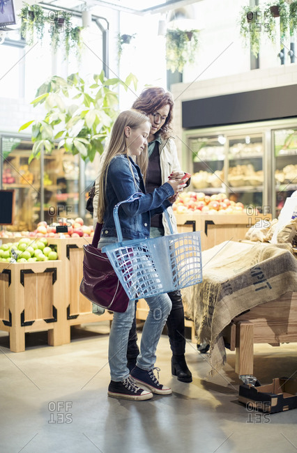 Full length of mother and daughter using mobile phone in grocery store