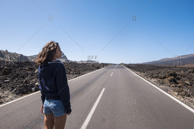 Young woman looking into the distance on road in Tenerife, Canary Islands, Spain