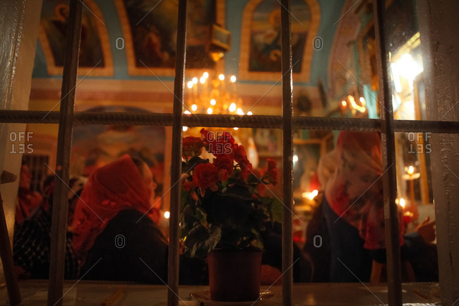 View through window of Orthodox Easter service in church in Vadeni village, Moldova 2017