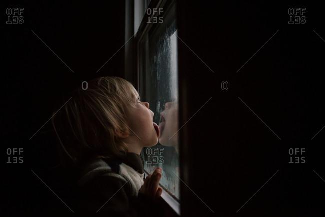 Boy licking a frosty window