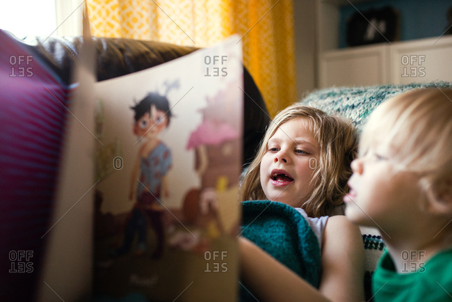 Girl reading book by toddler boy