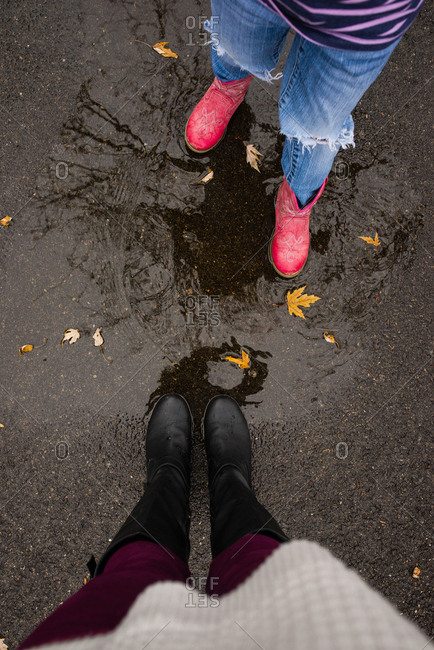 Two people in rain boots in puddle