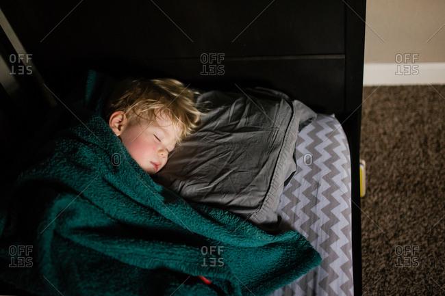 Boy asleep under cozy blanket