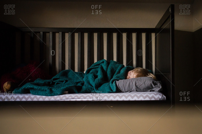 Toddler asleep in a child's bed