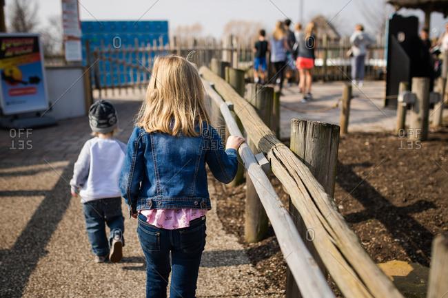 Two kids walking around petting zoo