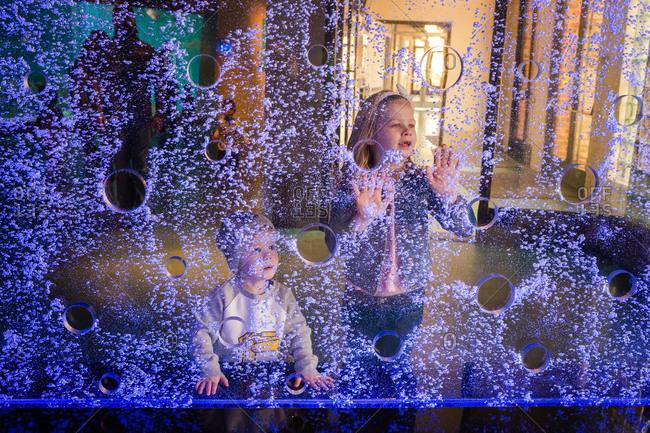 Kids by a blue light wall