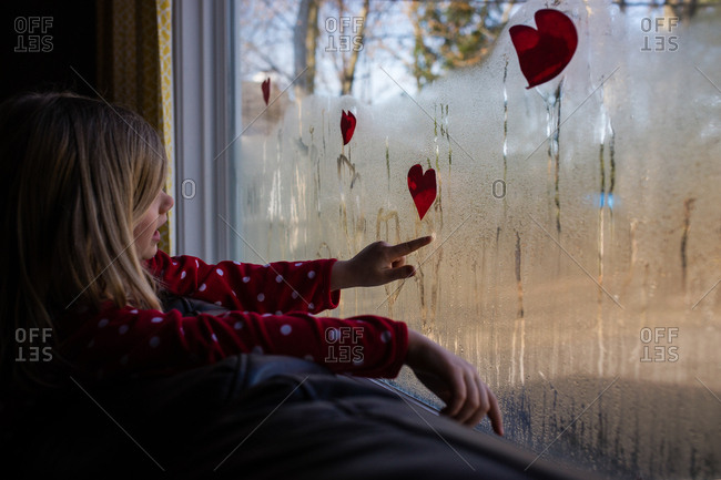 Girl drawing on window with hearts