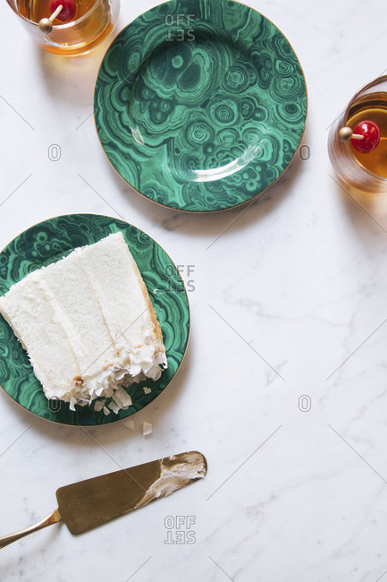 Piece of white layer cake on a green swirl plate