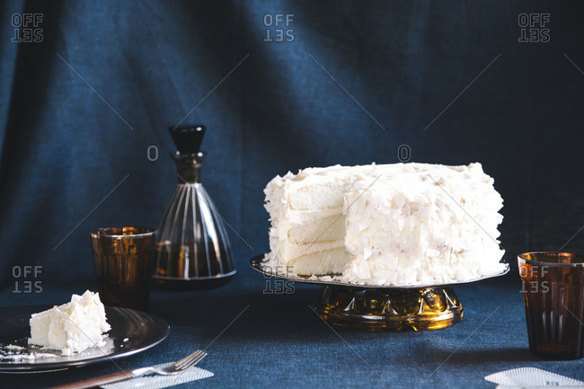 White layer cake on a brown glass cake stand with a piece missing