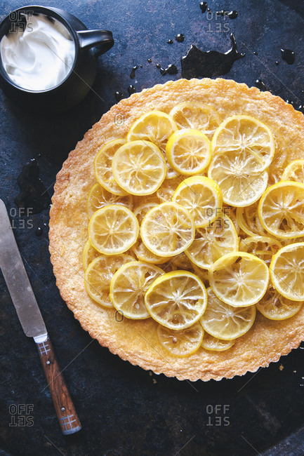 Whole baked pie topped with sliced lemons and a mug of whipped cream