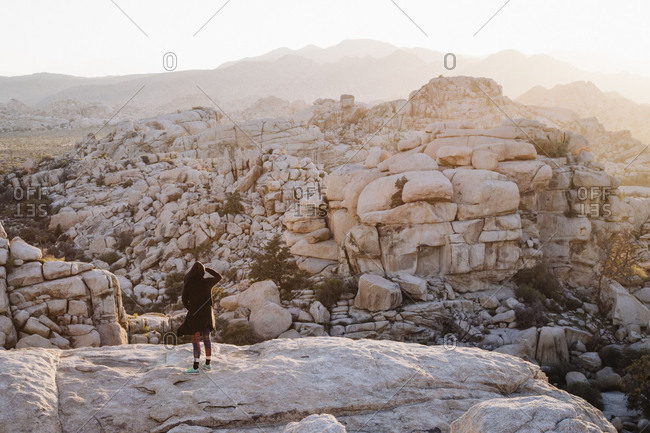Woman standing on a cliff overlooking stones in the desert