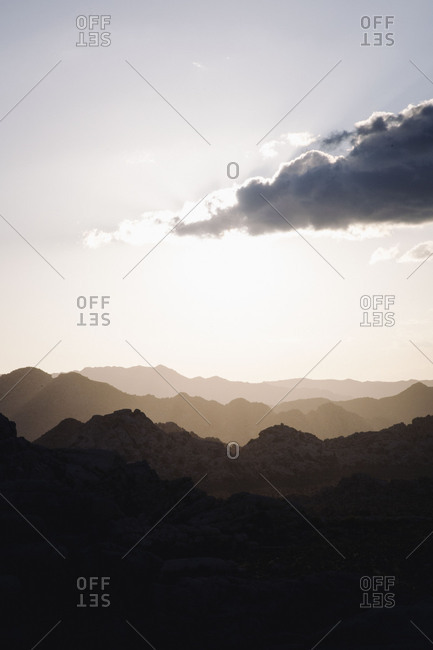 Sun setting behind a cloud over mountain ridges in the desert
