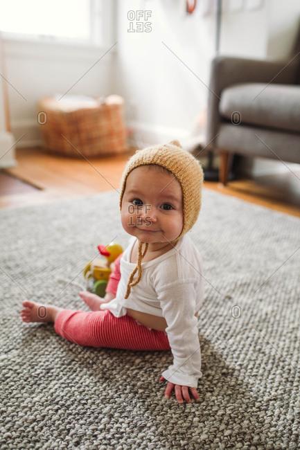 A baby in a knit bonnet
