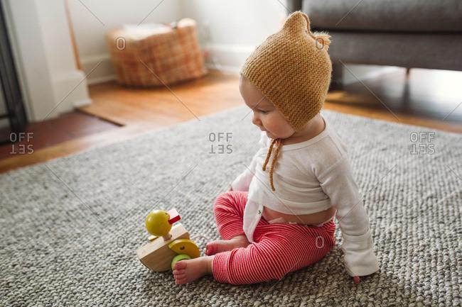 A baby on floor wearing knit bonnet