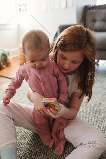 Girl showing baby sister books