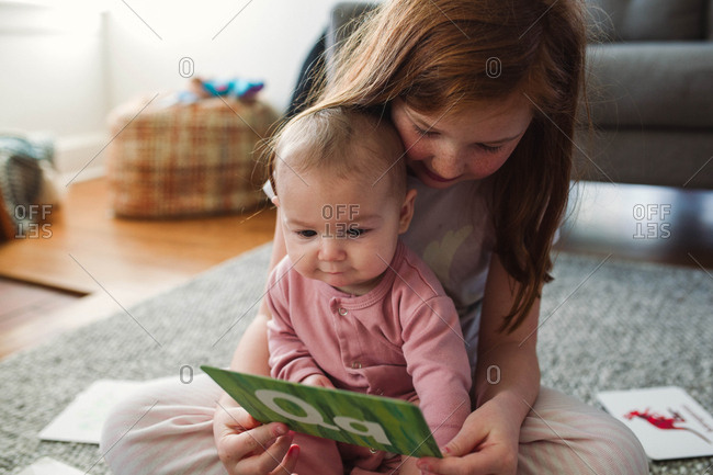 Girl showing baby sister letters