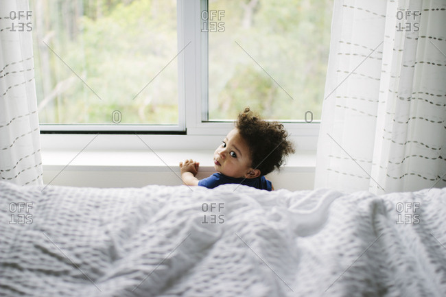 Baby boy standing at a window looking out