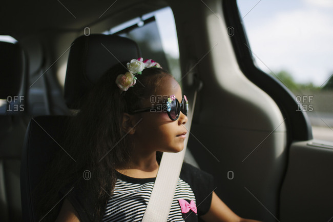 Little girl with sunglasses sitting in the backseat of a vehicle