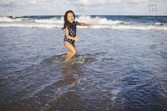 Little girl running and splashing in waves at the ocean