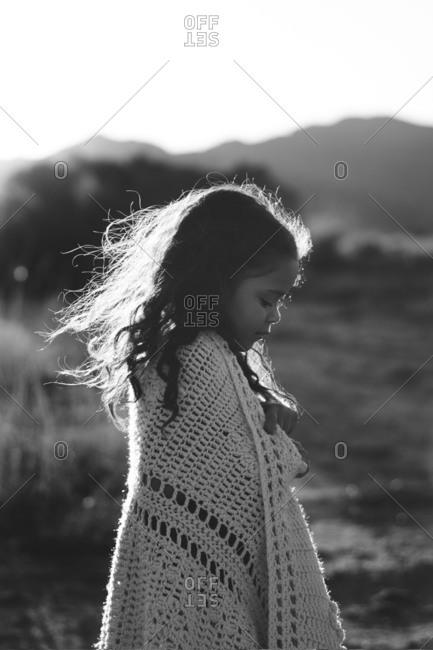 Girl wrapped in a knit blanket in a field