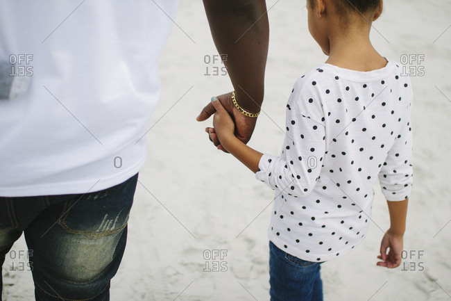 Father and daughter walking hand in hand on a beach