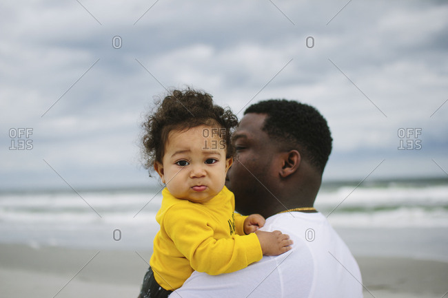 Father carrying his baby son on a beach