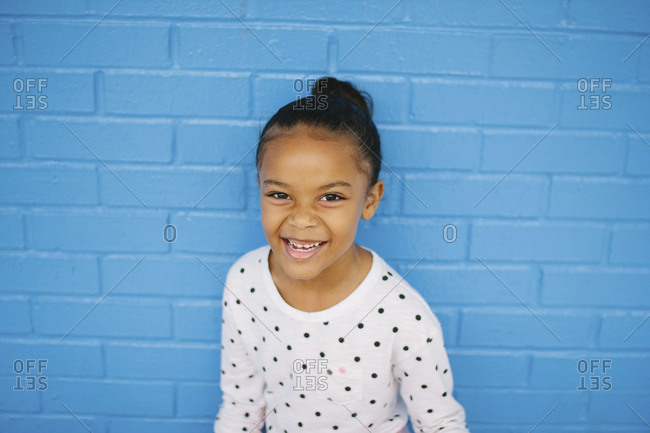 Little girl leaning against a blue brick wall smiling
