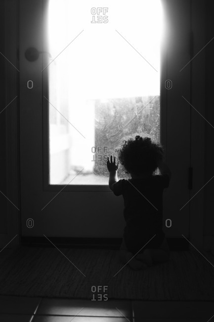 Silhouette of a baby boy looking out a window