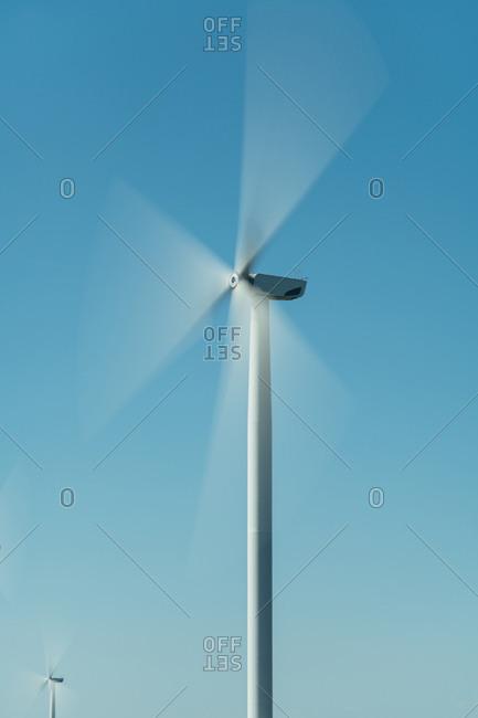 Wind turbine spinning against a blue sky