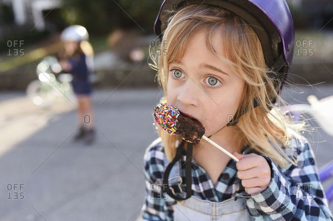 Little girl in a bike helmet eating a brownie on a stick