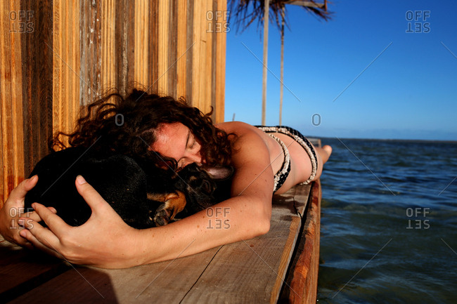 Young woman lying on a pier beside the ocean hugging a dog