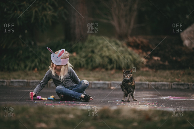 Girl wearing a bunny hat sitting on the ground next to her pet cat and drawing a picture with chalk on the driveway