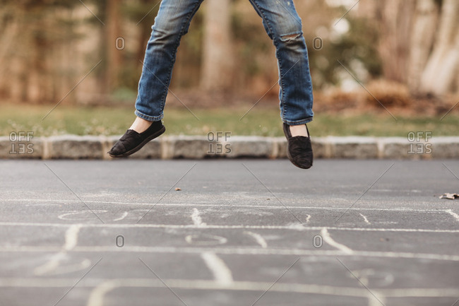 Girl jumping in air while playing hopscotch on driveway