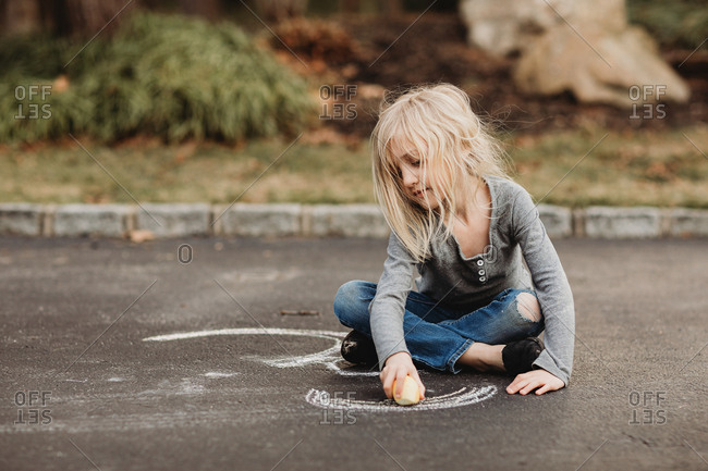 Girl sitting cross-legged drawing with a big piece of chalk on the driveway