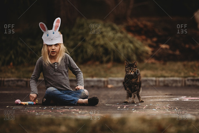 Girl wearing a bunny hat sitting on the ground with her pet cat next to sidewalk chalk drawings