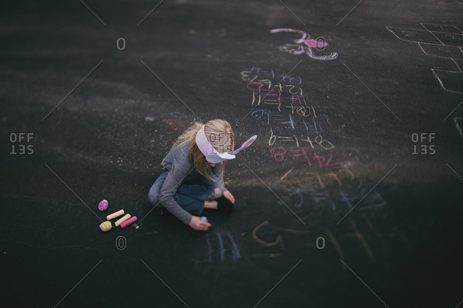 Girl wearing a bunny hat writing out math equations with chalk on driveway