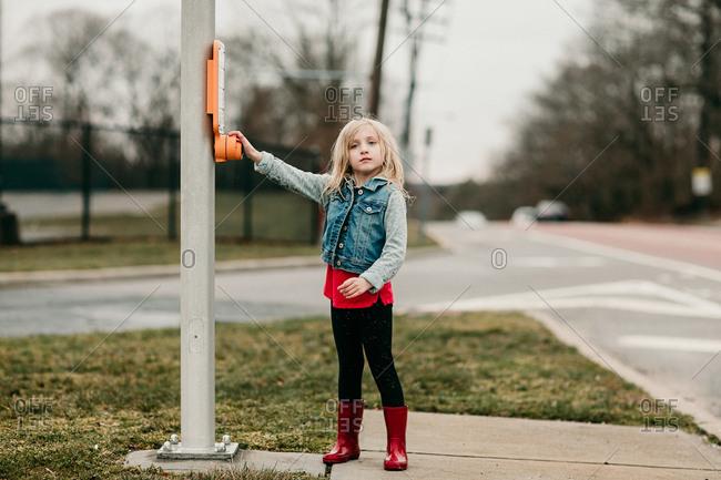 Girl standing on sidewalk pushing crosswalk button