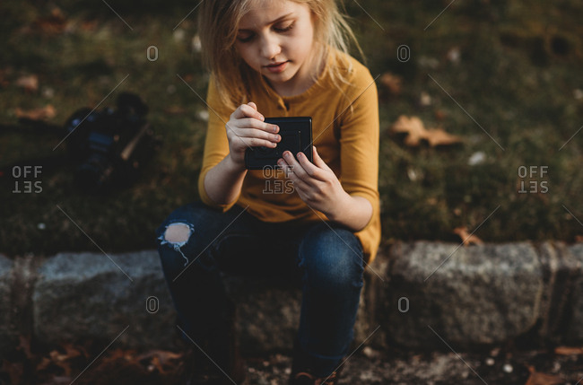 Girl sitting on stone curb holding camera