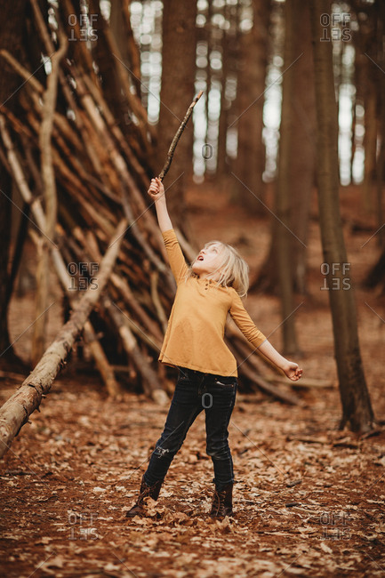 Girl holding up a stick outdoors in the forest