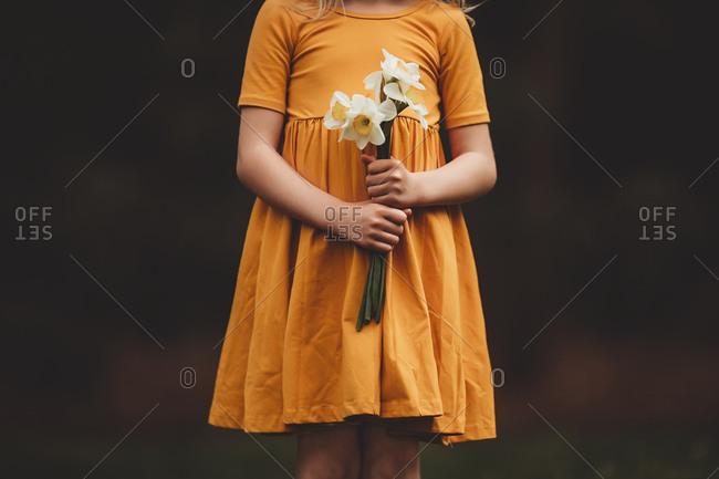 Girl holding freshly picked white daffodils