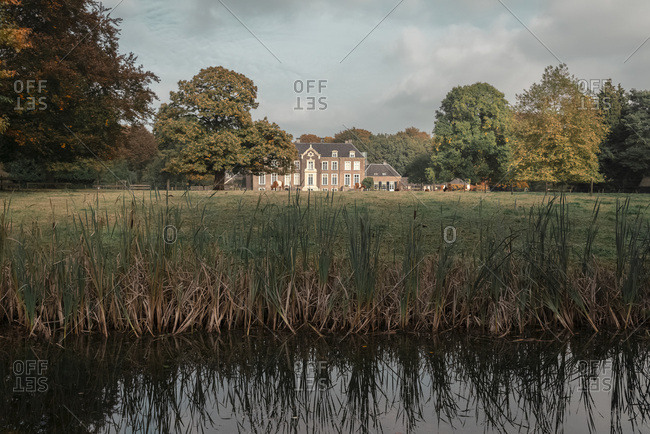 Dutch autumn rural landscape with mansion lit by sunlight.